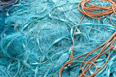 Abstract background with a pile of blue nylon fishing nets with a coiled rope on top ready to be cast overboard for a new days fishing and catch