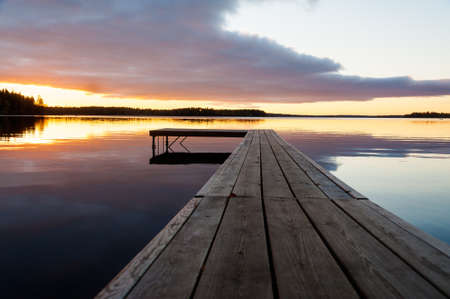 Beautful glowing orange sunset over a rustic timber plank jetty reflected in the mirror calm waters of the lake below, a background of natural beauty and serenity