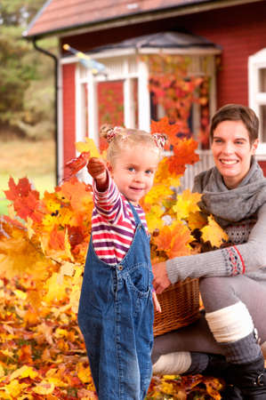Laughing young mother and her cute little daughter playing in colourful yellow and orange autumn leaves while collecting a basketful of leafy twigs to decorate the house photo