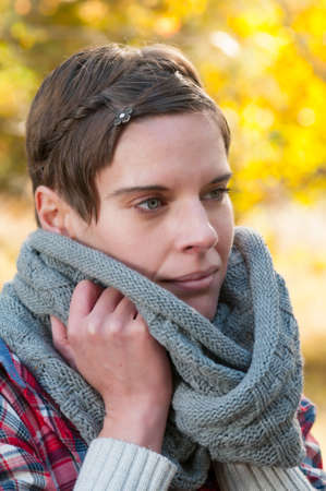 snuggling: Attractive shorthaired pensive woman snuggling into a warm knitted winter scarf