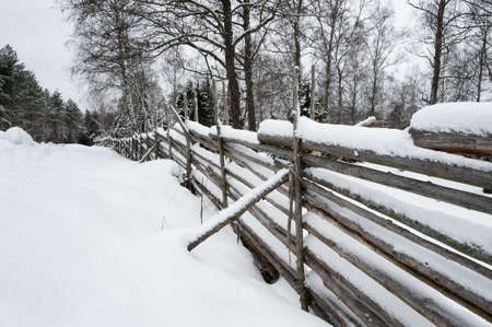 fenceline: Rustic wooden fence leading into woodland and forests covered in a thick layer of snow after a winter snowfall with a big snow drift in the foreground
