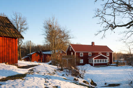 Typical red wooden houses in the country side of southern Sweden photo