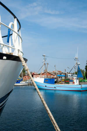 Boats moored in the harbour on the Island of Moen, Denmark with a mooring hawser in the foreground and view of the wharf behind Stock Photo - 18295855