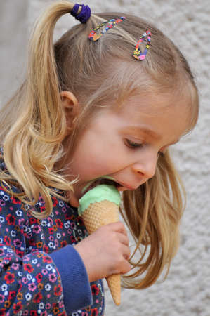 Cute little girl with blonde hair and pigtails eating ice cream Stock Photo