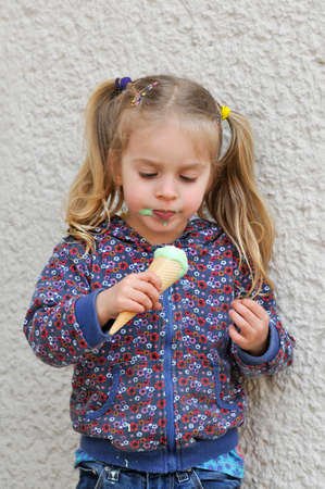 Cute little girl with blonde hair and pigtails eating ice cream photo