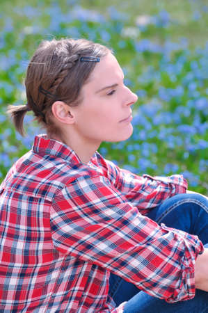 Young attractive woman sitting on a meadow with Scilla bifolia in spring photo