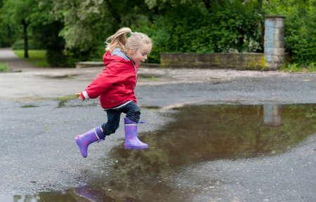 Niña muy linda en la chaqueta roja, pantalones de mezclilla y botas de goma está saltando en un charco en un día de lluvia