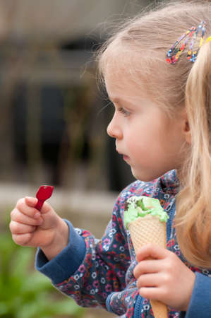 Very cute little blonde girl eating ice cream in a waffle photo
