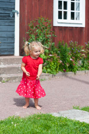 Little blond girl with pigtails in a red summer dress in the garden in front of a typical red wooden house in Sweden Stock Photo