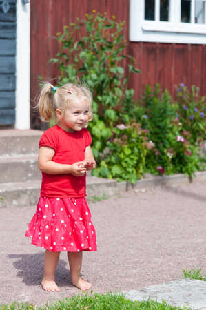 Little blond girl with pigtails in a red summer dress in the garden in front of a typical red wooden house in Sweden photo