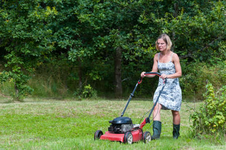 Young blond woman cutting grass with a lawn mower