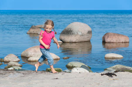 Cute little girl walking barefoot on the beach and enjoying the bright summer day photo