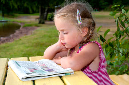 Little girl sittingon a park bench at a lake and reads newspaper