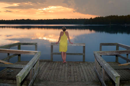 Young woman standing on a pier and admired the sunset on a lake in Småland, Sweden