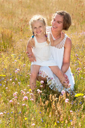 Beautiful young mother and her cute little daughter dressed in white summer dresses, sitting on a meadow with wild flowers on a warm summer day   photo