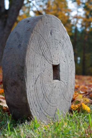 antik: Very old handmade grindstone with geometric engraving on the surface to find the center for making the hole