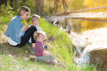 Mother and her two little children sitting at the shore of a small river in Sweden and watching beavers photo