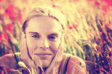 Beautiful young woman in a cornfield with blooming poppies, textured portrait photo