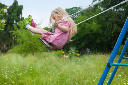 Cute little girl with long blonde hair swinging in the garden Imagens