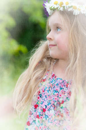 Cute little girl with a wreath of flowers in her blonde hair  Textured picture in vintage style  photo