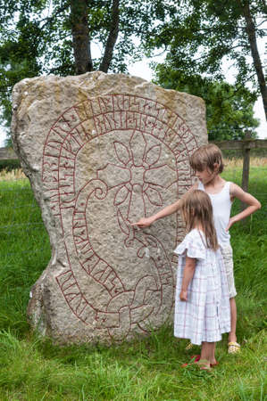 Two children study the  rune stone of Bj�rby after a bath in the Baltic Sea nearby photo