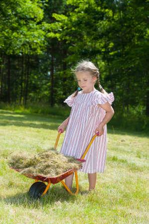 Happy little girl in summer dress in the garden with wheel barrow full of hay photo