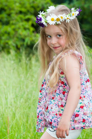 Cute happy little girl with a flower wreath at Midsummer photo
