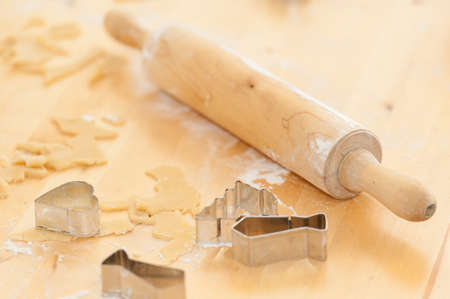 Rolling pin and different cake cutters, dough and flour on a table, used for preparing christmas cookies and gingerbread photo