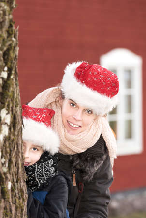 Attractive woman and her little son wearing christmas caps and having fun together out in the garden photo