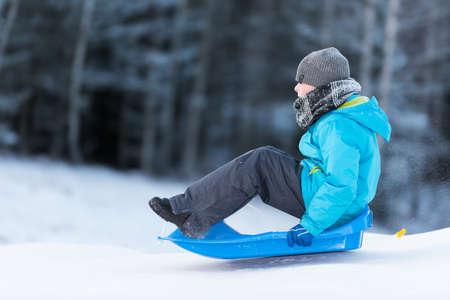 sledging: Giovane ragazzo slittino discesa om una slitta blu in una giornata invernale Archivio Fotografico