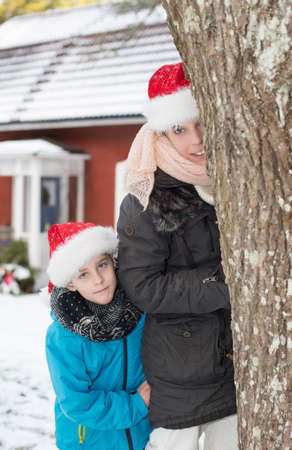 Attractive happy woman with santa claus hat and her little son looking from behind a tree i front of a typical red wooden house in Sweden. photo