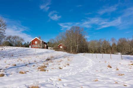 Red hölzerne Bauernhaus in Schweden unter einem klaren blauen Himmel im Winter. Weitwinkelaufnahme Standard-Bild - 36846292