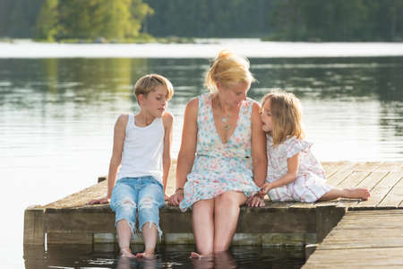 Beautiful young mother and her two kids sitting on a jetty in the summer sun, bathe the feet in the water, and enjoy a beautiful day in midsummer.