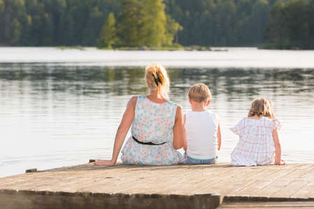 Young mother and her two kids sitting on a jetty in the summer sun