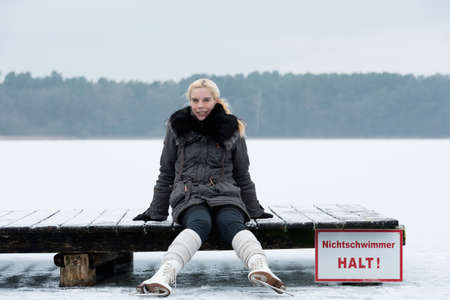 Young woman takes a break while skating and sitting on a jetty.