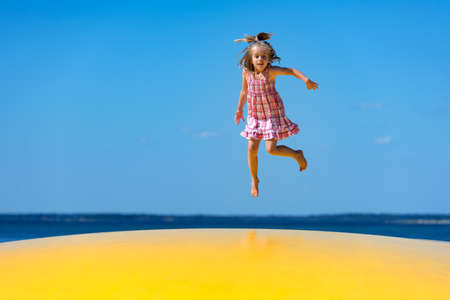Cute little girl with pigtail jumping on to inflatable trampoline at the beach.