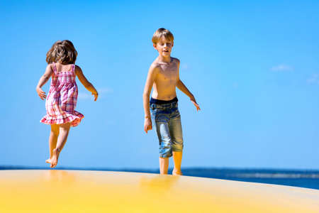 blowup: Two kids, a girl and a boy, jumping on to inflatable trampoline and having fun