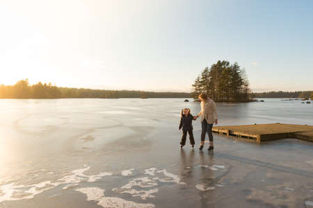 Mother and her little daughter scating on th eice of a frozen lake in the light of a sunny afternoon in winter. Imagens