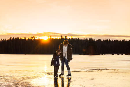 Mother and daughter scating together on the ice of a frozen lake in Sweden in the light of the late afternoon.