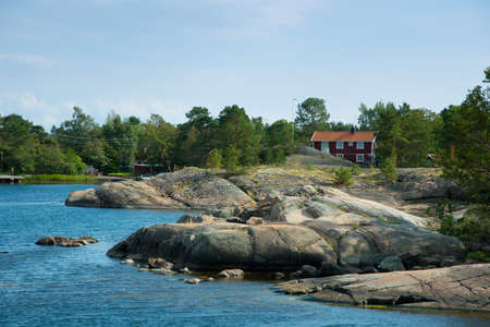 Swedish coast near Oskashamn, Småland, with smooth polished  rocks and red farmhouse