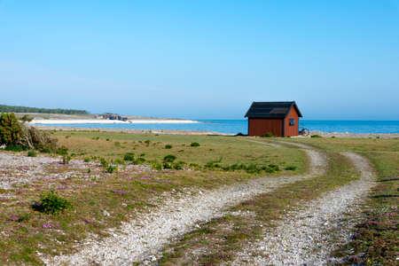 Matin d'été sur la côte de Féroé, Suède, avec cabane de pêcheur et chemin de terre