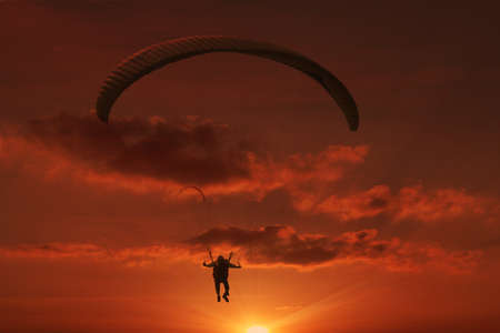 Paraglider flying against a sunset photo