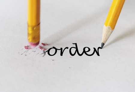 order chaos: Eraser deleting the word Disorder Stock Photo