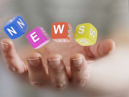 hand holding four cubes with news sign