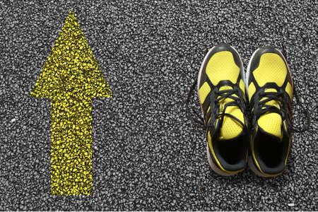 Sport shoes and arrow on asphalt background