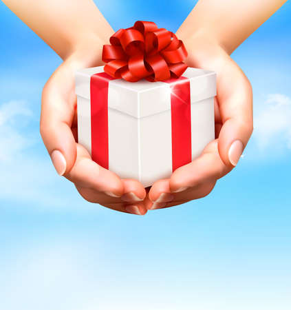 desember: Holiday background with hands holding gift boxes. Concept of giving presents