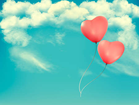 Valentine heart-shaped balloons in a blue sky with clouds.