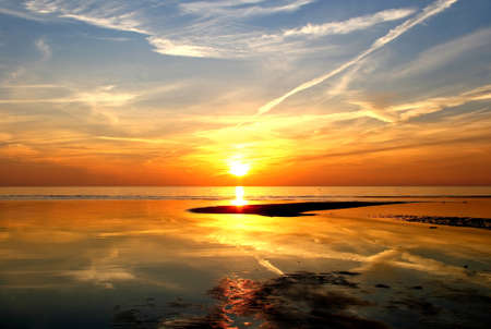 Beautiful sunset over the Riga Bay in Saulkrasti. Sun is almost fall down to the sea, cloudscape is reflecting on the water. Stock Photo