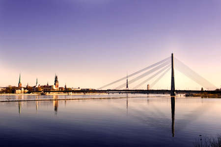 Classic view of Old Riga in Latvia. Cable-stayed bridge over the river of Daugava and Riga castle with Riga Cathedral in a front. TV tower, railway bridge and Saint Peter's church in a background.