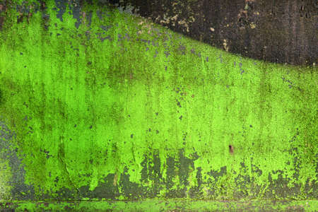 Grunge background / texture on a cracked green stone wall with splashes of paint.